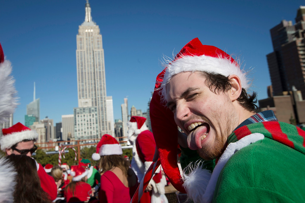 . Revelers dressed in holiday theme costumes participate in SantaCon on a rooftop bar  Saturday, Dec. 13, 2014, in New York.  SantaCon organizers retained lawyer Norman Siegel  last week as part of an effort to tame the excesses of the daylong party.  Siegel said the government cannot ban SantaCon. But he said the government can reasonably regulate the event. (AP Photo/John Minchillo)