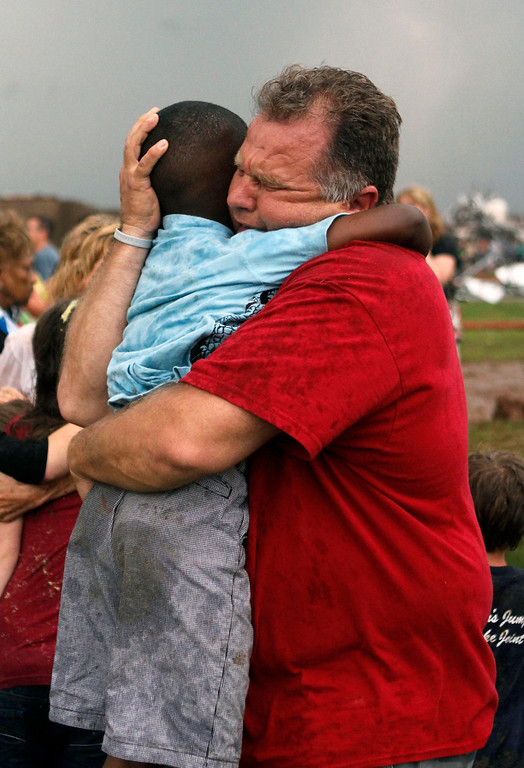 . A teacher hugs a child at Briarwood Elementary school after a tornado destroyed the school in south Oklahoma City, Monday, May 20, 2013. A monstrous tornado roared through the Oklahoma City suburbs, flattening entire neighborhoods with winds up to 200 mph, setting buildings on fire and landing a direct blow on an elementary school. (AP Photo/The Oklahoman, Paul Hellstern)