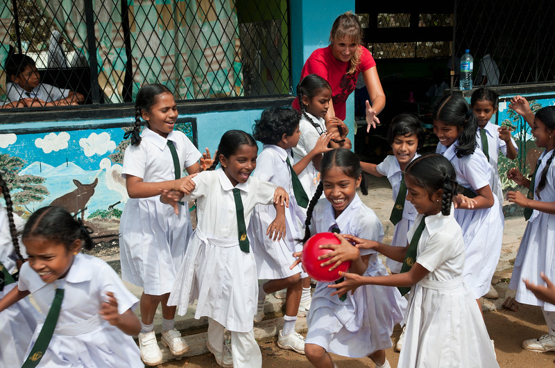 Volunteer tosses girls a ball during recess at the Sulaimanya Muslim School in Galle, Sri Lanka.