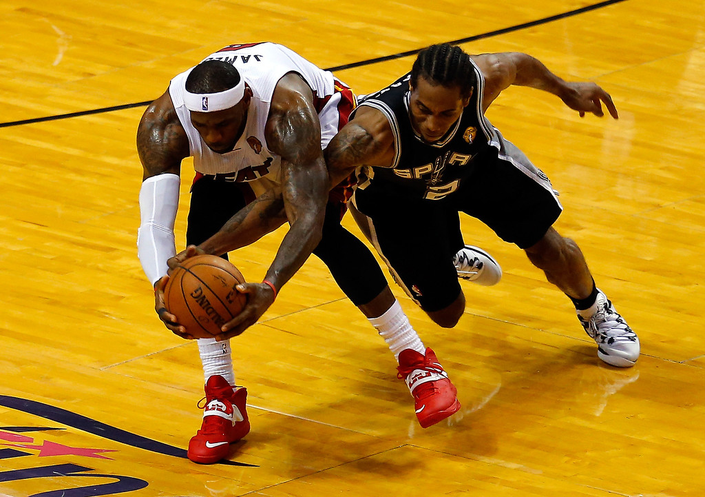 . MIAMI, FL - JUNE 12:  LeBron James #6 of the Miami Heat and Kawhi Leonard #2 of the San Antonio Spurs battle for a loose ball during Game Four of the 2014 NBA Finals at American Airlines Arena on June 12, 2014 in Miami, Florida. (Photo by Chris Trotman/Getty Images)