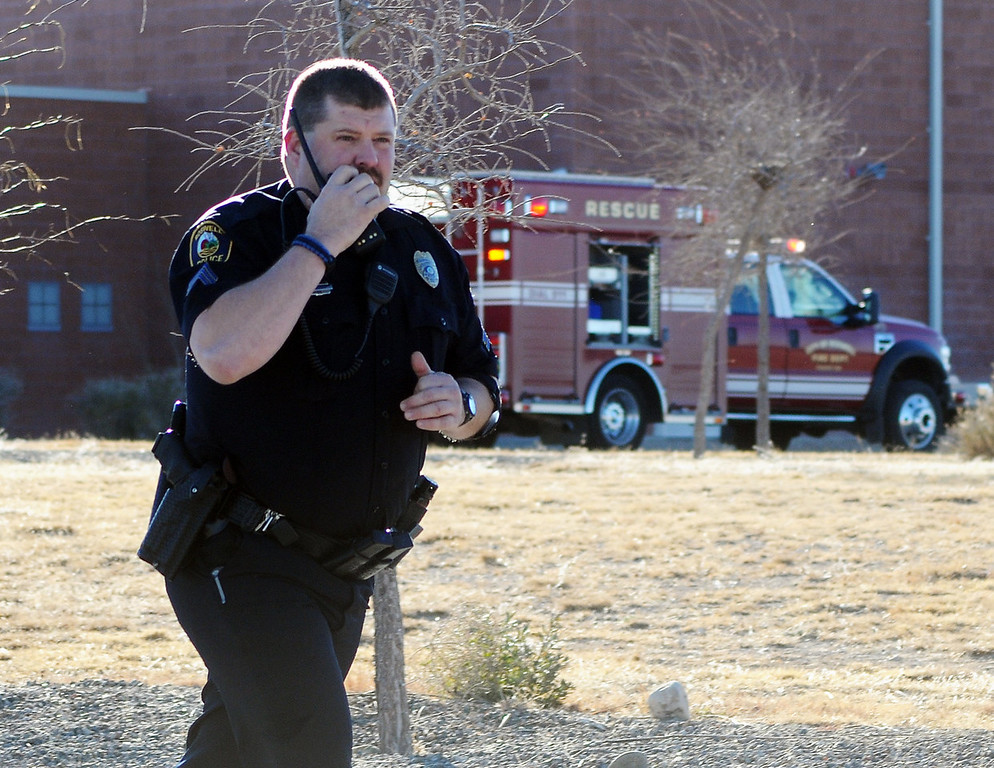 . Law enforcement personnel set up a perimeter after a shooting at Berrendo Middle School, Tuesday, Jan. 14, 2014, in Roswell, N.M. A shooter opened fire at the middle school, injuring at least two students before being taken into custody. (AP Photo/Roswell Daily Record, Mark Wilson)