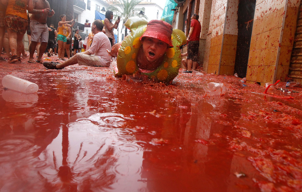 """. A man lays on a puddle of tomato juice during the annual \""""tomatina\"""" tomato fight fiesta in the village of Bunol, 50 kilometers outside Valencia, Spain, Wednesday, Aug. 28, 2013. Thousands of people are splattering each other with tons of tomatoes in the annual \""""Tomatina\"""" battle in recession-hit Spain, with the debt-burdened town charging participants entry fees this year for the first time. Bunol town says some 20,000 people are taking part in Wednesday\'s hour-long street bash, inspired by a food fight among kids back in 1945. Participants were this year charged some 10 euros ($13) to foot the cost of the festival. Residents do not pay. (AP Photo/Alberto Saiz)"""