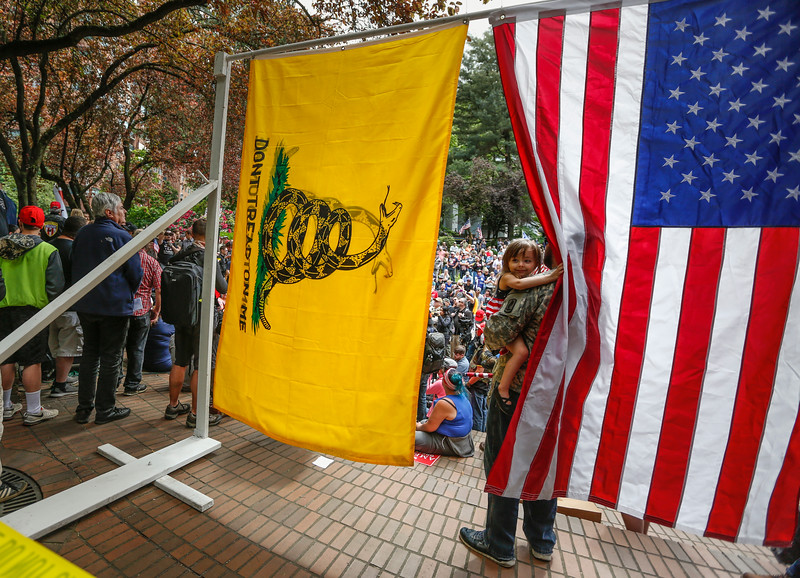 A young girl moves an American flag to see other protesters during competing protests in Portland, Oregon on June 4, 2017.
