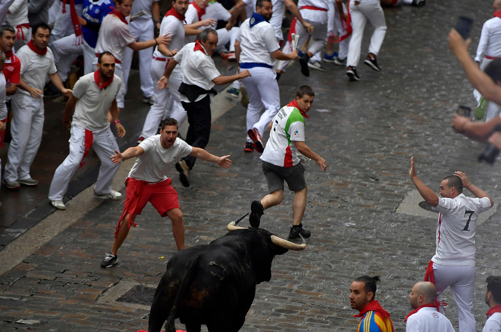 . Revellers run next to Puerto de San Lorenzo\'s fighting bulls during the running of the bulls at the San Fermin Festival, in Pamplona, northern Spain, Saturday, July 7, 2018. Revellers from around the world flock to Pamplona every year to take part in the eight days of the running of the bulls. (AP Photo/Alvaro Barrientos)