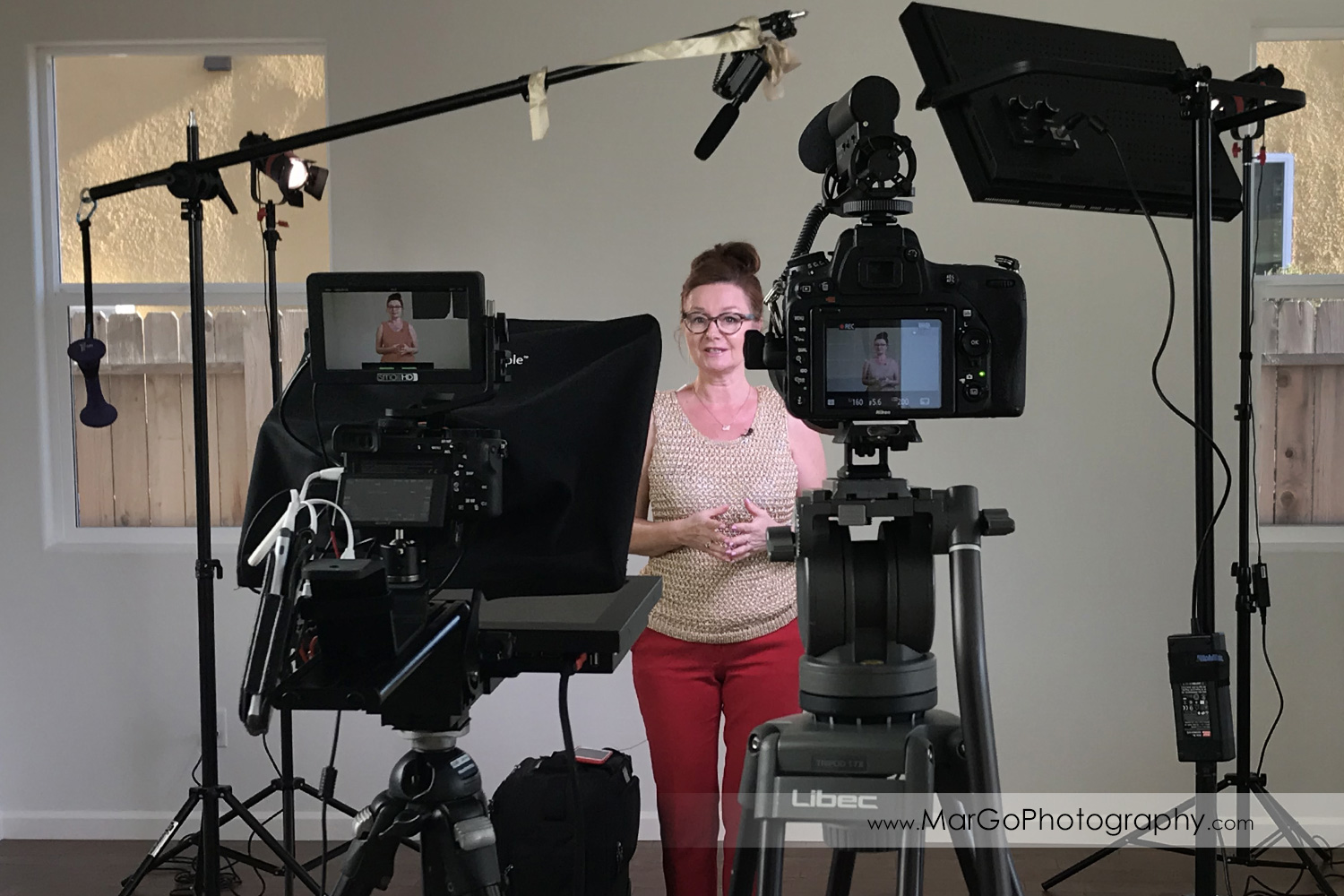 behind the scenes of indoor filming woman speaker in golden top and red pants seen through two cameras and teleprompter setup