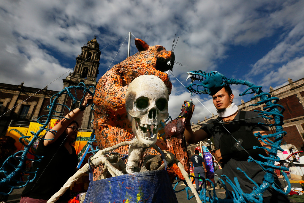 . A man decorates a sculpture of skulls on display as part of the Day of the Dead festivities in Mexico City, Thursday, Oct. 27, 2016. The holiday honors the dead as friends and families gather in cemeteries to decorate their loved ones\' graves and hold vigil through the night on Nov. 1 and 2. (AP Photo/Marco Ugarte)