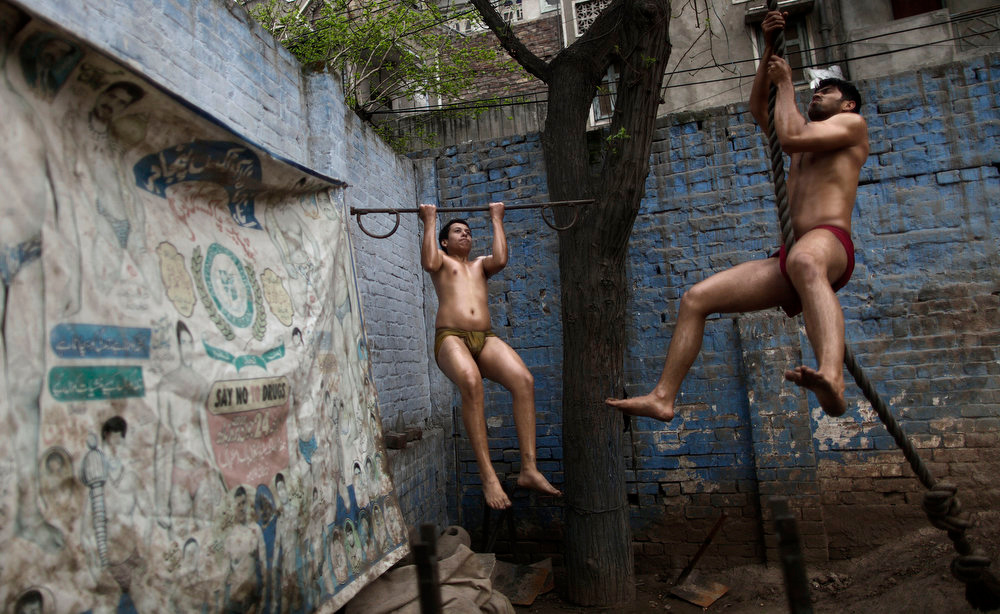 Description of . Pakistani Kushti wrestlers warm up before training, at a wrestling club in Lahore, Pakistan, Tuesday, Feb. 26, 2013. Kushti, an Indo-Pakistani form of wrestling, is several thousand years old and is a national sport in Pakistan. (AP Photo/Muhammed Muheisen)