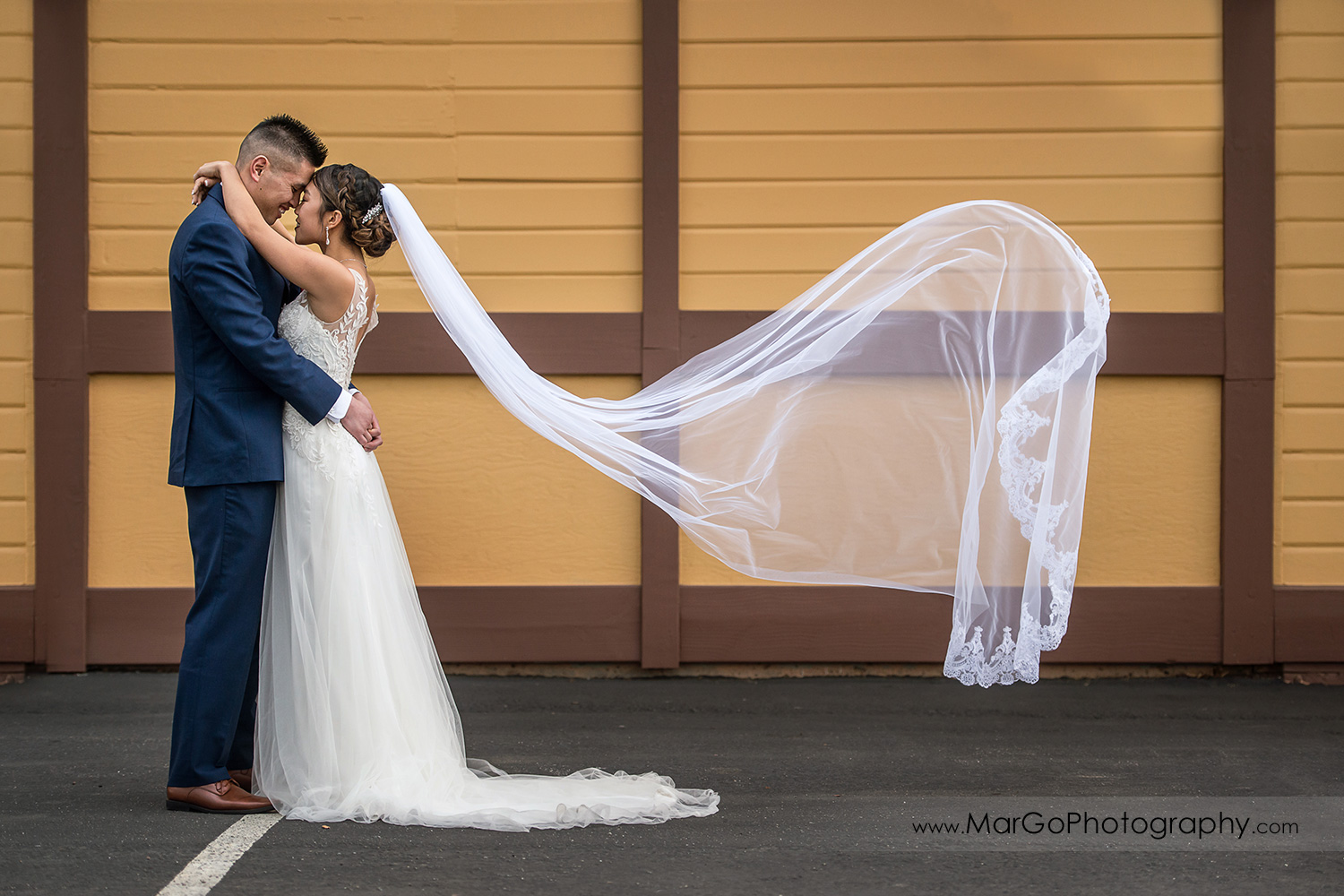 veil shot of bride and groom touching foreheads at train station near Sunol's Casa Bella