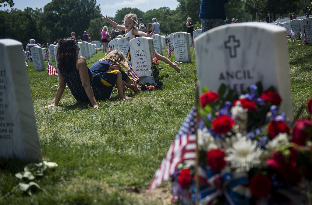 . Angela Spraul, with her daughters Alana, 6,  sitting, and Ava, 4, visit the grave of her husband John Spraul, U.S. Navy, who died Feb. 28, 2013, at Section 60 on Memorial Day at Arlington National Cemetery on May 25, 2015 in Arlington, Va. U.S. President Barack Obama, Chairman of the Joint Chiefs of Staff U.S. Army General Martin Dempsey and U.S. Defense Secretary Ash Carter honored fallen soldiers during a ceremony at Arlington on this Memorial Day.  (Photo by Gabriella Demczuk/Getty Images)