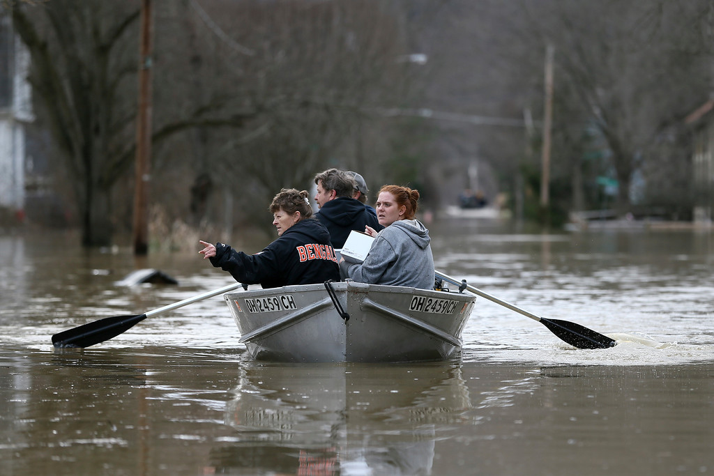 . Lesa Tomlin, left, gestures toward dry land as Lori Sullender, right, holds medicine for her father-in-law pulled from a Rohde Avenue home in California, Sunday, Feb. 25, 2018, in Cincinnati. Heavy rains overnight have sent the swollen Ohio River at Cincinnati to its highest point in 20 years with the river expected to remain above flood stage through the end of the week, a National Weather Service meteorologist said Sunday. (Kareem Elgazzar/The Cincinnati Enquirer via AP)