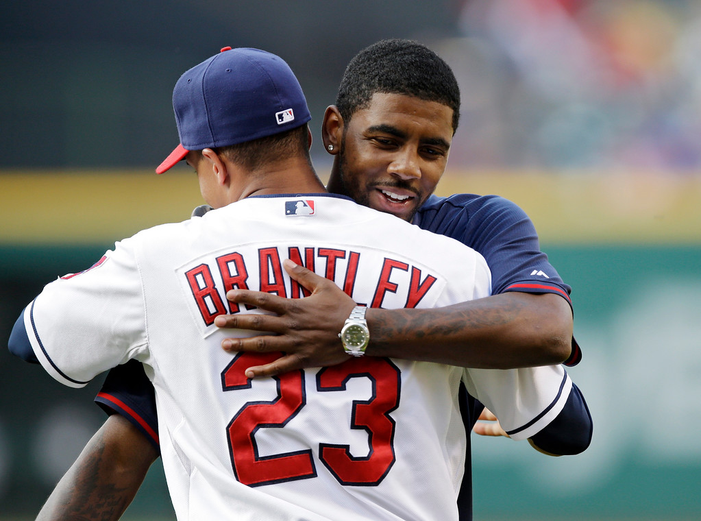 . Cleveland Cavaliers point guard Kyrie Irving hugs Cleveland Indians\' Michael Brantley (23) after a ceremonial pitch before a baseball game against the Los Angeles Angels Monday, June 16, 2014, in Cleveland. (AP Photo/Mark Duncan)