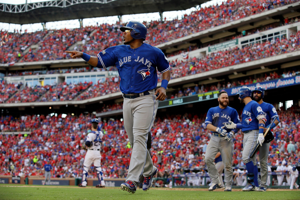 . Toronto Blue Jays\' Edwin Encarnacion, front, celebrates after scoring on a bases-clearing triple by Troy Tulowitzki in the third inning of baseball Game 1 of the American League Division Series against the Texas Rangers on Thursday, Oct. 6, 2016, in Arlington, Texas. (AP Photo/LM Otero)