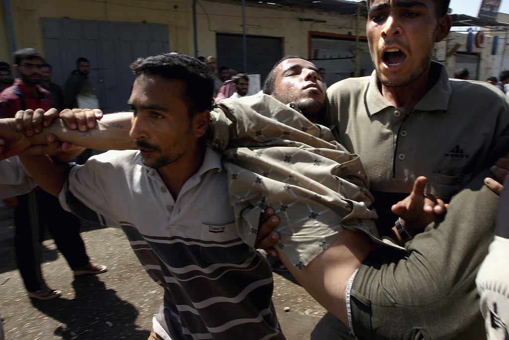 . Iraqi Shiite demonstrators carry an injured man as bullets fly overhead on August 26, 2004 in Najaf, Iraq. (Photo by Ghaith Abdul-Ahad/Getty Images)