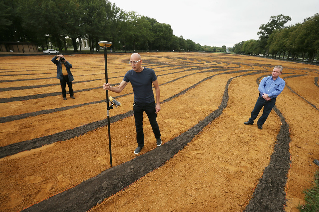 . Cuban-American artist Jorge Rodriguez-Gerada demonstrates how a \'rover,\' or high-precision GPS marker, was used to create his six-acre sand and soil \'facescape\' on the JFK Hockey Field along the north side of the Reflecting Pool on the National Mall October 1, 2014 in Washington, DC. (Photo by Chip Somodevilla/Getty Images)