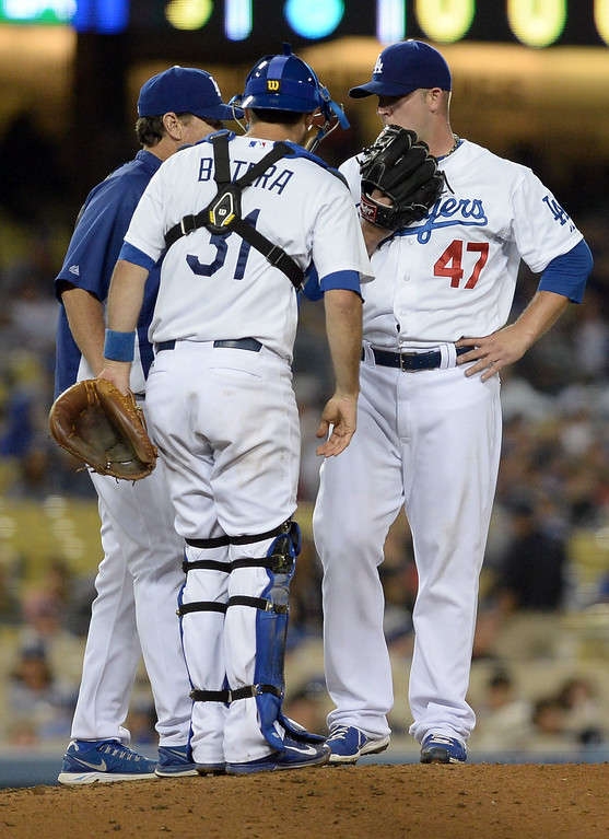 . Los Angeles Dodgers relief pitcher Paul Maholm talks with catcher Drew Butera and coach Rick Honeycutt against the Cleveland Indians July 1, 2014 in Los Angeles.(Andy Holzman/Los Angeles Daily News)