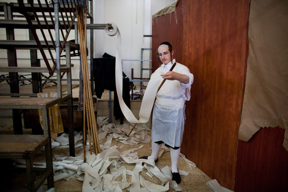 . An Ultra-Orthodox Jewish man wraps a stick with paper before preparing the Matzoth, or unleavened bread, in a final preparation before the start at sundown of the Jewish Pesach (Passover) holiday on March 25, 2013 in Bnei Brak, Israel. Religious Jews throughout the world eat matzoth during the eight-day Passover, or Pesach, holiday, The Jewish holiday commemorates the Israelis\' exodus from Egypt some 3,500 years ago and their ancestors\' plight by refraining from eating leavened food. Passover begins March 25 and ends on the evening of April 02.  (Photo by Uriel Sinai/Getty Images)