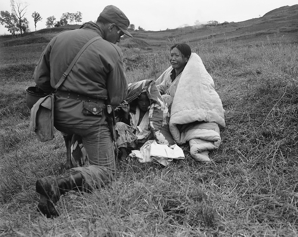 . A North Korean mother who fled to the fields keeps her children under wraps as she tries to explain her problems to a U.S. paratrooper who landed in the area near Sunchon, North Korea on Oct. 25, 1950 during operation to out off escape route of fleeing Reds. (AP Photo/Max Desfor)