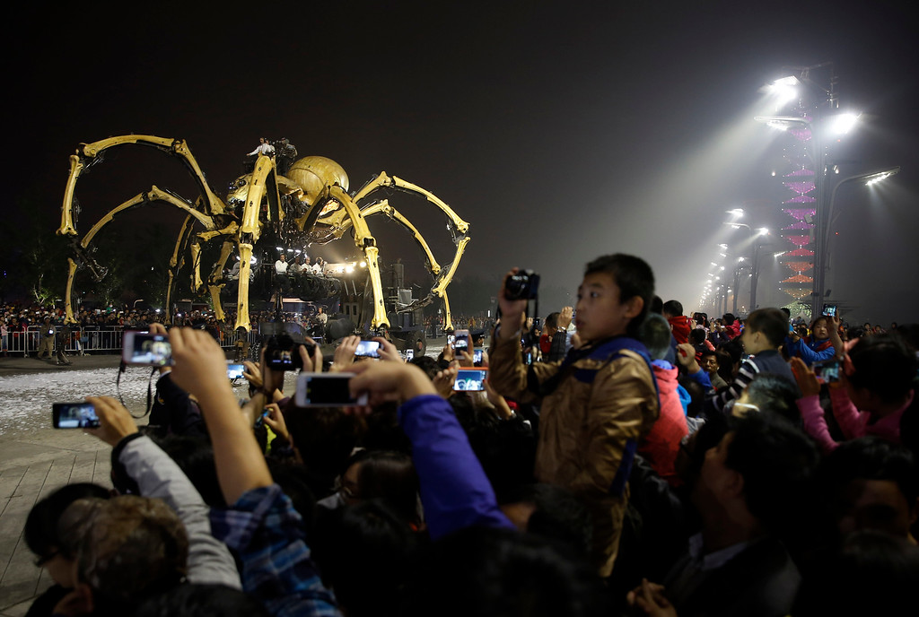 . People take photos of the French production company La Machine\'s mechanical spider also known as La Princesse appears during a performance held in front of the Bird\'s Nest Stadium in Beijing, China Sunday, Oct. 19, 2014. (AP Photo/Andy Wong)