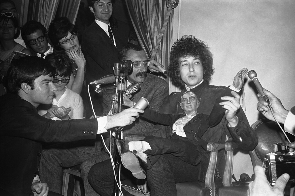 . American folk singer Bob Dylan sits with a puppet as he faces the media during a press conference at the Hotel George V in Paris, France on May 23, 1966. He will appear on Tuesday at the Paris Olympia music-hall. (AP Photo/Pierre Godot)