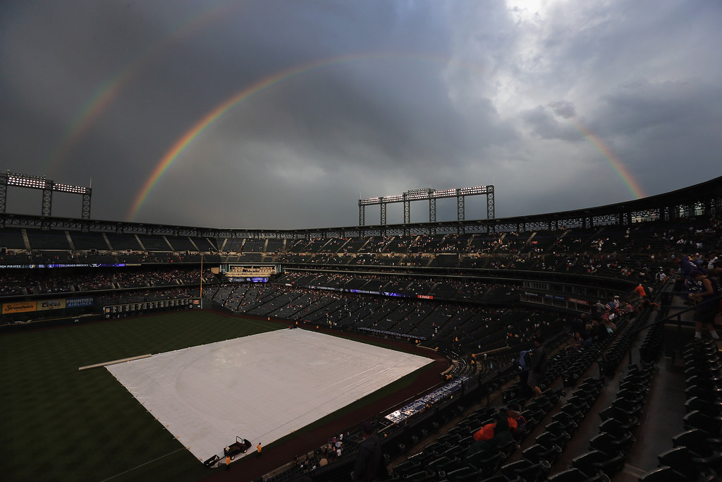 . DENVER, CO - AUGUST 10:  A rainbow archs over the stadium and the tarp covers the infield as weather delayed the start of the game between the Pittsburgh Pirates and the Colorado Rockies  at Coors Field on August 10, 2013 in Denver, Colorado.  (Photo by Doug Pensinger/Getty Images)