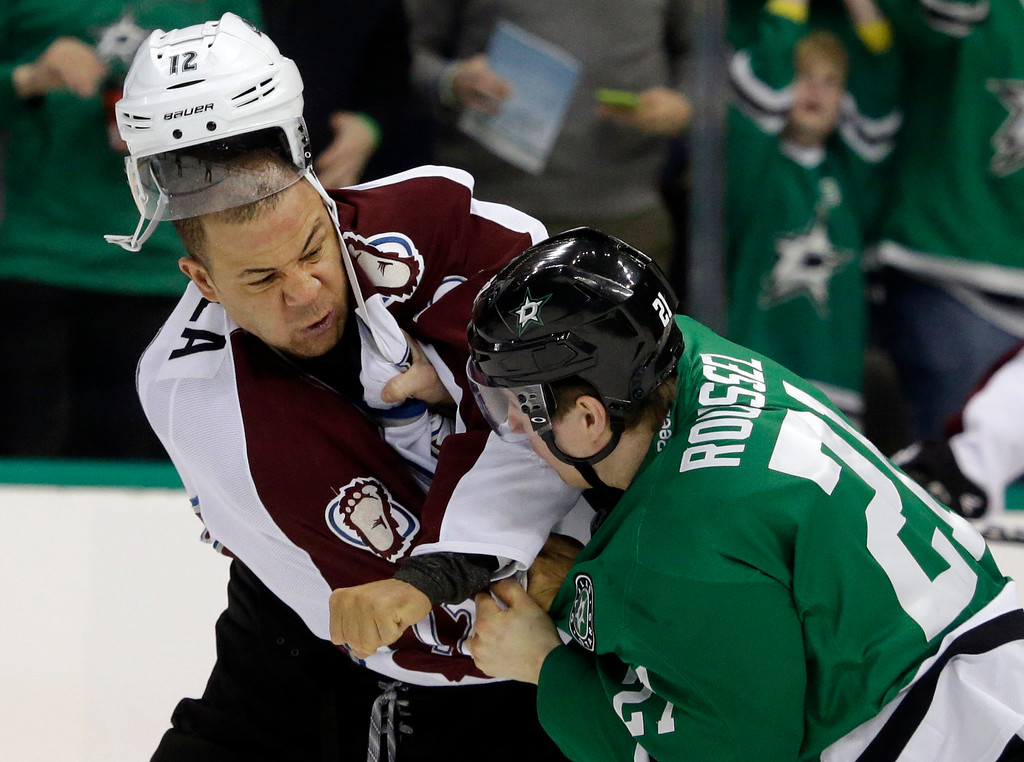 . Colorado Avalanche right wing Jarome Iginla (12) and Dallas Stars left wing Antoine Roussel (21) fight during the first period of an NHL hockey game Tuesday, Feb. 3, 2015, in Dallas. (AP Photo/LM Otero)