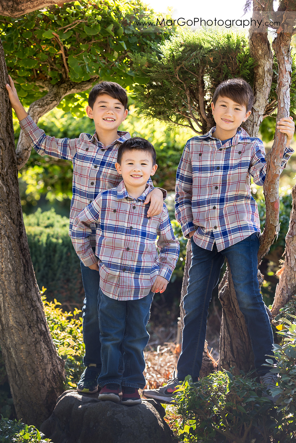 full body portrait of three boys in gray shirts looking into camera at Hayward Japanese Garden