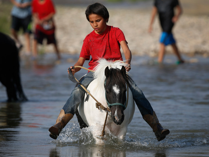 Nate Tsosie rides his horse Bandit through the river during the centennial celebration of the annual Crow Fair in Crow Agency, Mont. on Thursday, Aug.16, 2018.