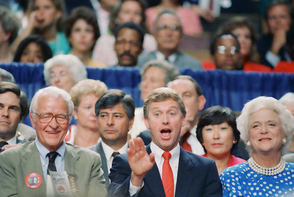 . Sen. Dan Quayle waves as he sits with Mrs. Barbara Bush and Indiana Gov. Robert Orr at session of the Republican National Convention in New Orleans  Wednesday, August 17, 1988. Quayle is George Bush�s selection for a running mate in the presidential race. (AP Photo/Dennis Cook)
