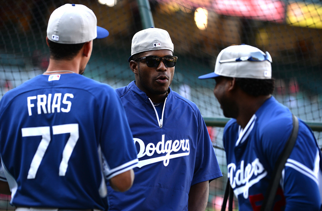 . Los Angeles Dodgers\' Yasiel Puig, center talks with teammates Carlos Frias (77) and Pedro Baez prior to a baseball game against the Los Angeles Angels at Anaheim Stadium in Anaheim, Calif., on Thursday, Aug. 7, 2014.  (Photo by Keith Birmingham/ Pasadena Star-News)