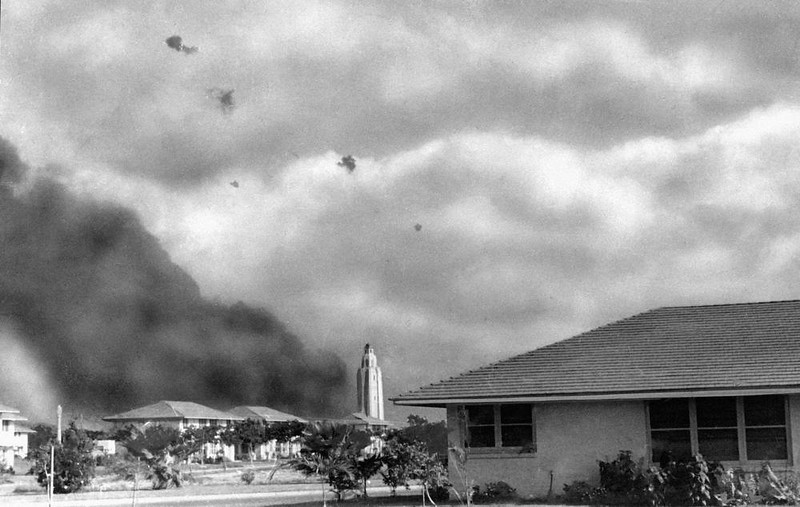 ". Japanese plane, proceeds toward ""Battleship Row\"" at Pearl Harbor after other bombers had hit USS Arizona, from which smoke billows, Dec. 7, 1941. Photo was taken from the yard of Army\'s Hickam Field Quarters by Mrs. Mary Naiden of New York City. (AP Photo)"
