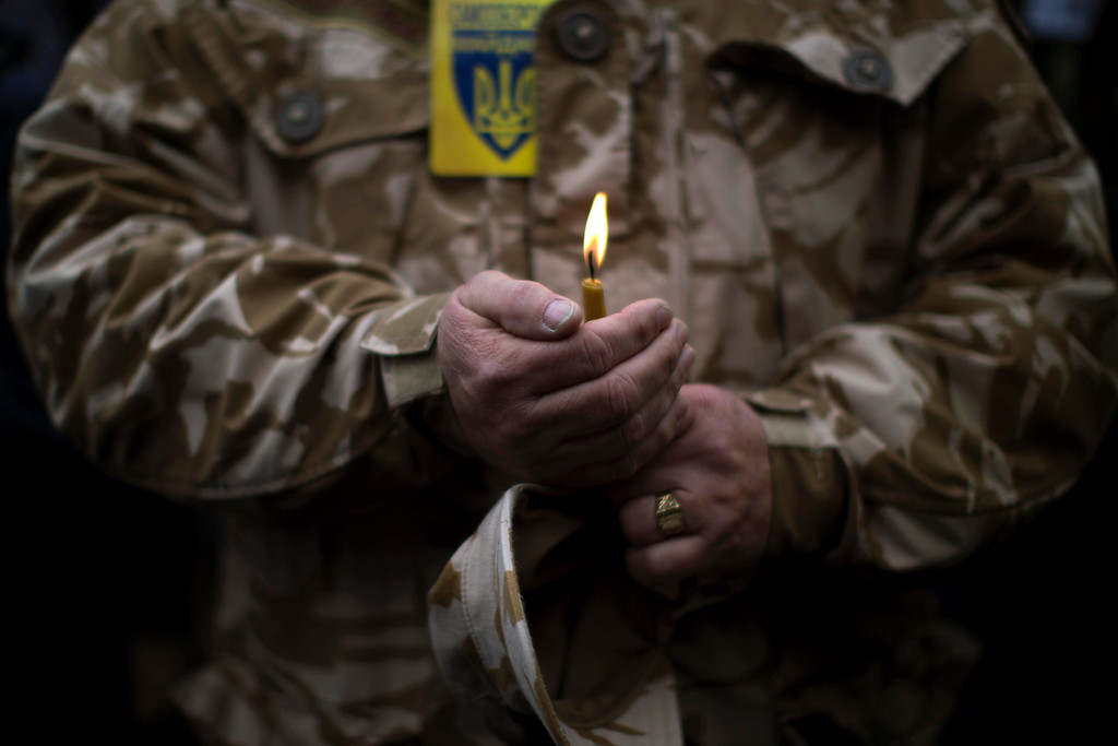 . A man wearing camouflage uniform holds a candle during the funeral of Volodymyr Topiy, 59, who was found burned in the house of trade unions in Kiev\'s Independence Square during recent clashes with police, Ukraine, Tuesday, March 4, 2014.  (AP Photo/Emilio Morenatti)