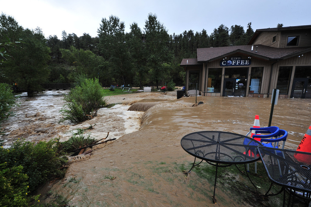 . Coffee-colored water streams past local businesses on Friday, September 13, 2013. WIth an additional six inches of overnight rainfall, all rivers and streams are well out of their banks, completely flooding downtown Estes Park. Walt Hester/Estes Park Trail-Gazette