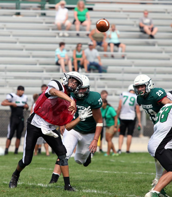 . Randy Meyers - The Morning Journal Columbia quarterback Jared Bycznski throws to a back while under pressure by the Elyria Catholic defense during a scrimmage.
