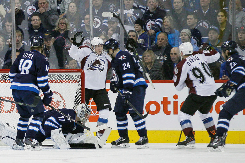 . Colorado Avalanche\'s Ryan O\'Reilly (90) and Matt Duchene (9) celebrate O\'Reilly\'s goal on Winnipeg Jets goaltender Ondrej Pavelec (31) as Jets\' Bryan Little (18) and Grant Clitsome (24), Chris Thorburn (22) look on during the second period of an NHL game, Thursday, Dec. 12, 2013 in Winnipeg, Manitoba. (AP Photo/The Canadian Press, John Woods)