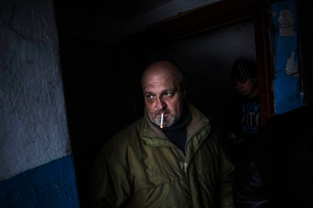 . A Ukrainian man waits for shelling to abate as he shelters inside a building after a Ukrainian army shell hit a bus stop in the Kievsky district in Donetsk, Ukraine, Tuesday, Jan. 20, 2015. At least three civilians were killed in shelling Tuesday in eastern Ukraine as fighting continued between government and rebel forces in the separatist-held city of Donetsk. (AP Photo/Manu Brabo)