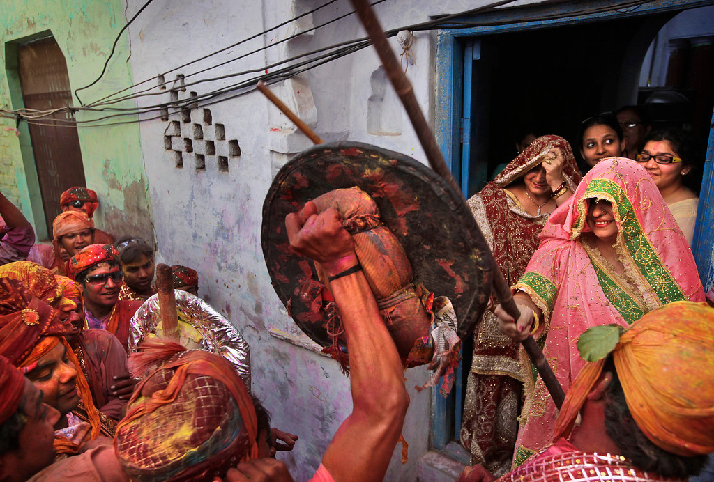 . An Indian woman from the village of Barsana hits villagers from Nandgaon with a wooden stick during the Lathmar Holy festival the legendary hometown of Radha, consort of Hindu God Krishna, in Barsana, 115 kilometers (71 miles) from New Delhi, India, Thursday, March 21, 2013. During Lathmar Holi the women of Barsana beat the men from Nandgaon, the hometown of Krishna, with wooden sticks in response to their teasing as they depart the town. (AP Photo/Manish Swarup)