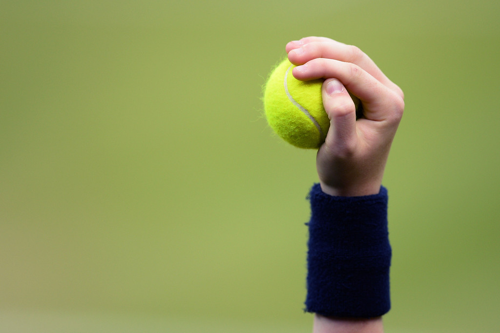 . LONDON, ENGLAND - JULY 02:  A ballboy holds a tennis ball aloft during the Ladies\' Singles quarter-final match between Petra Kvitova of Czech Republic and Kirsten Flipkens of Belgium on day eight of the Wimbledon Lawn Tennis Championships at the All England Lawn Tennis and Croquet Club at Wimbledon on July 2, 2013 in London, England.  (Photo by Mike Hewitt/Getty Images)