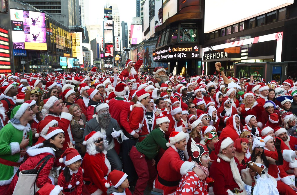 . People dressed as Santa Claus and Mrs. Claus celebrate in Times Square as they gather for the annual Santacon festivities on December 13, 2014 in New York. AFP PHOTO/DON  EMMERT/AFP/Getty Images
