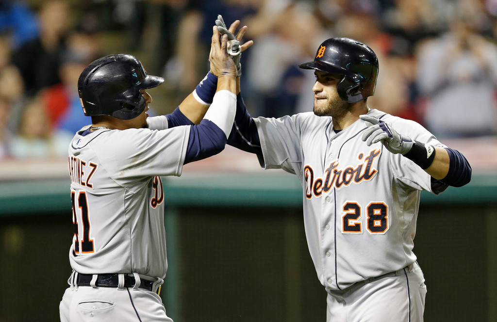 . Detroit Tigers\' J.D. Martinez, right, is congratulated by Victor Martinez after hitting a three-run home run off Cleveland Indians relief pitcher John Axford in the eighth inning of a baseball game on Friday, June 20, 2014, in Cleveland. Victor Martinez and Miguel Cabrera also scored on the hit. (AP Photo/Tony Dejak)