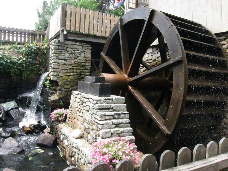 The wooden wheel of a grist mill is turned by the power of water