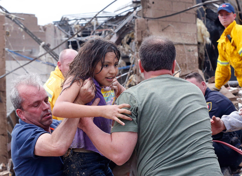 . A child is pulled from the rubble of the Plaza Towers Elementary School in Moore, Okla., and passed along to rescuers Monday, May 20, 2013. A tornado as much as a mile (1.6 kilometers) wide with winds up to 200 mph (320 kph) roared through the Oklahoma City suburbs Monday, flattening entire neighborhoods, setting buildings on fire and landing a direct blow on an elementary school.(AP Photo Sue Ogrocki)