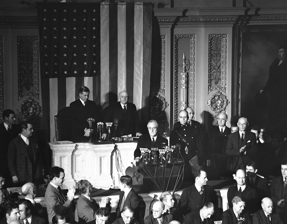. Declaring Japan guilty of a dastardly unprovoked attack, President Franklin D. Roosevelt asked Congress to declare war, Dec. 8, 1941. Listening are Vice President Henry Wallace, left, and House Speaker Sam Rayburn. (AP Photo)