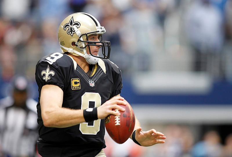 . New Orleans Saints quarterback Drew Brees looks downfield against the Dallas Cowboys in the first half of their NFL football game in Arlington, Texas December 23, 2012.  REUTERS/Mike Stone