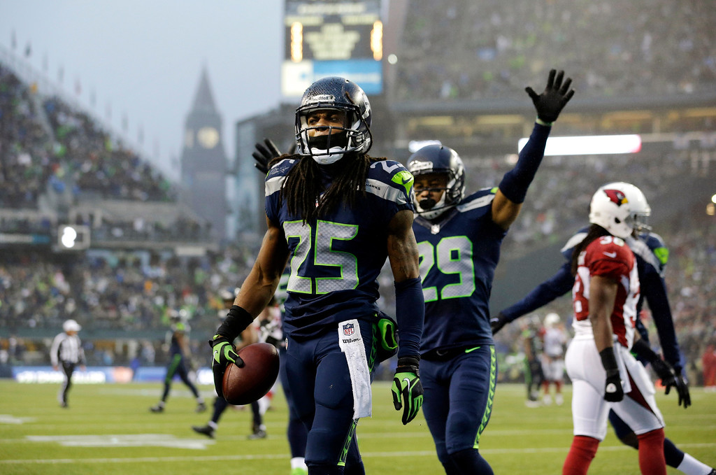 . Seattle Seahawks Richard Sherman (25) comes up with the football as Seahawks\' Earl Thomas (29) celebrates after Sherman intercepted an Arizona Cardinals pass in the second half of an NFL football game, Sunday, Dec. 22, 2013, in Seattle. (AP Photo/Elaine Thompson)