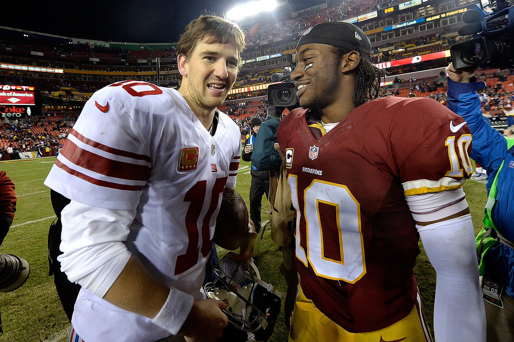 . LANDOVER, MD - DECEMBER 01:  Robert Griffin III #10 of the Washington Redskins talks with Eli Manning #10 of the New York Giants after the Giants defeated the Redskins 24-17 during an NFL game at FedExField on December 1, 2013 in Landover, Maryland.  (Photo by Patrick McDermott/Getty Images)