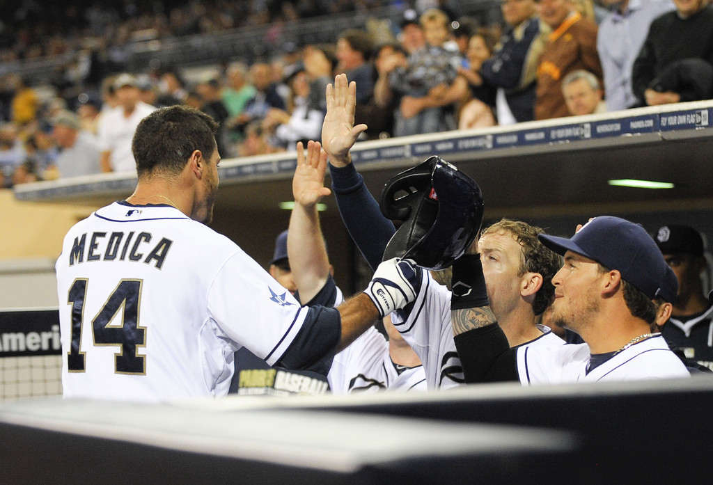 . SAN DIEGO, CA - APRIL 16:  Tommy Medica #14 of the San Diego Padres is congratulated after hitting a solo home run during the second inning of a baseball game against the Colorado Rockies at Petco Park April 16, 2014 in San Diego, California.  (Photo by Denis Poroy/Getty Images)