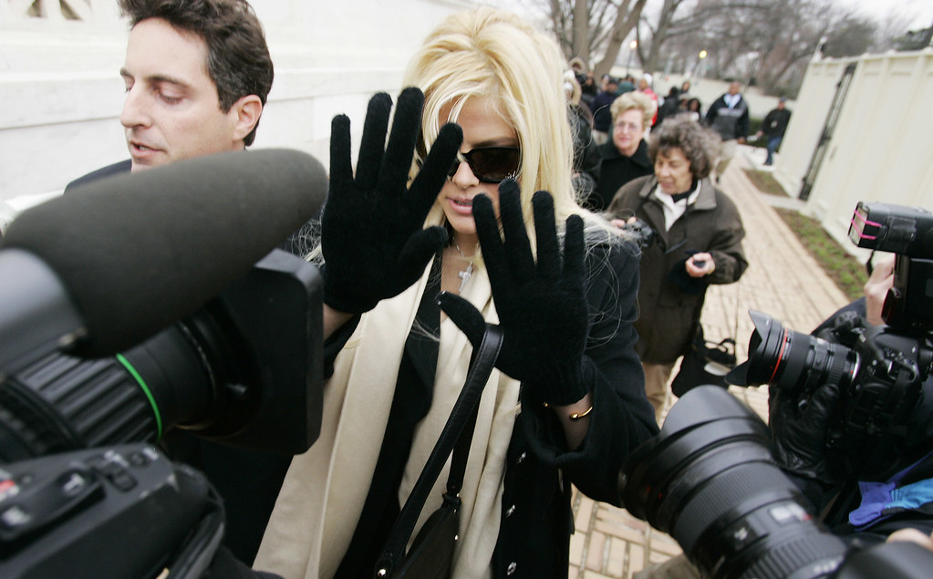 . Anna Nicole Smith, with her lawyer Howard K. Stern, left, tries to shield herself from cameras as she arrives at the U.S. Supreme Court, Tuesday, Feb. 28, 2006, in Washington. With an oil fortune on the line, former stripper Anna Nicole Smith encountered a sympathetic audience at the Supreme Court on Tuesday. (AP Photo/Manuel Balce Ceneta)