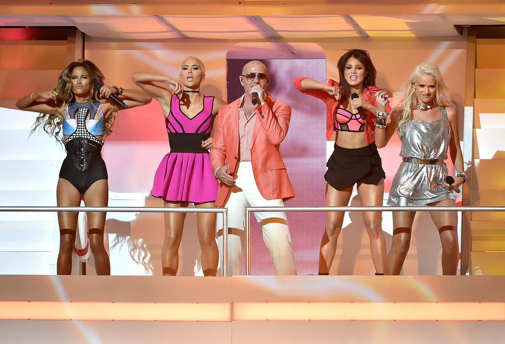 . LOS ANGELES, CA - MAY 01:  Rapper/host Pitbull (C) and (L-R) singers Emmalyn Estrada, Paula Van Oppen, Natasha Slayton, and Lauren Bennett of G.R.L. perform onstage during the 2014 iHeartRadio Music Awards held at The Shrine Auditorium on May 1, 2014 in Los Angeles, California. iHeartRadio Music Awards are being broadcast live on NBC.  (Photo by Kevin Winter/Getty Images for Clear Channel)