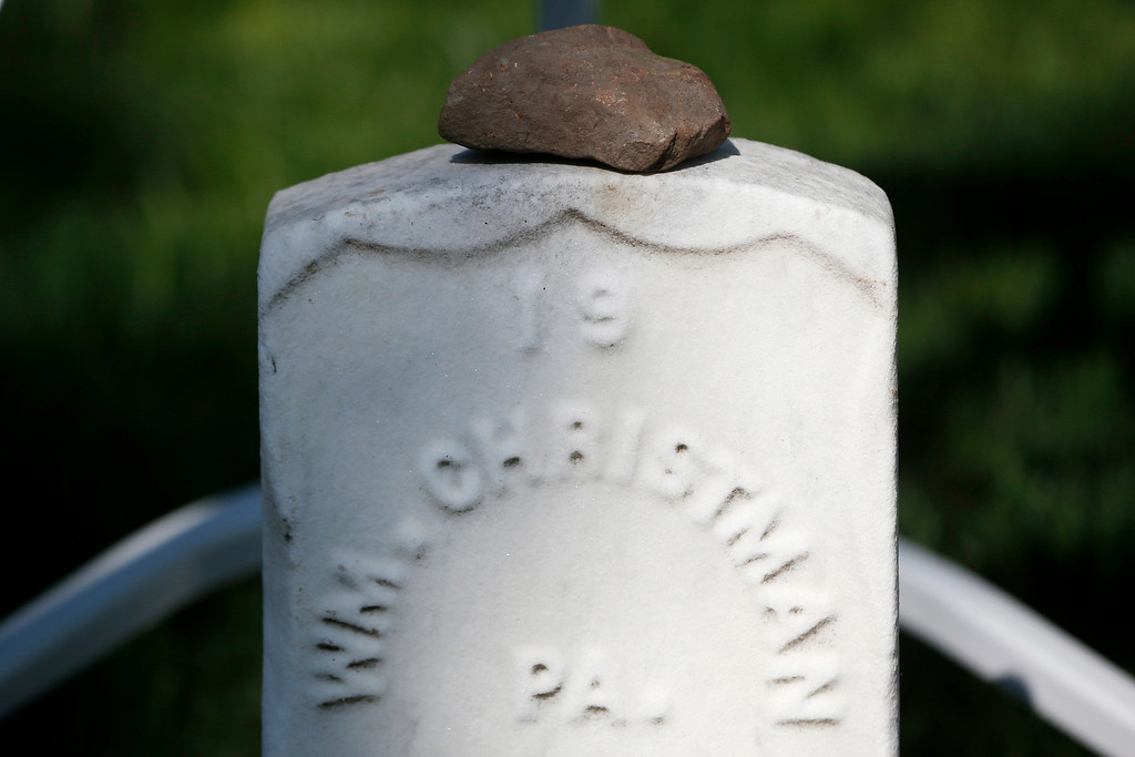 . A stone of remembrance sits on the gravestone of Army Pvt. William Christman, who was the first military burial at the cemetery, marking the beginning of commemorations of the 150th anniversary of Arlington National Cemetery in Arlington, Va., Tuesday, May 13, 2014. The stone is from the original Christman home that still stands in Pocono Lake, Pennsylvania. Christman, 20, enlisted in the 67th Pennsylvania Infantry and was hospitalized for measles five weeks later, dying on May 11, 1864 and buried at Arlington on May 13. (AP Photo)
