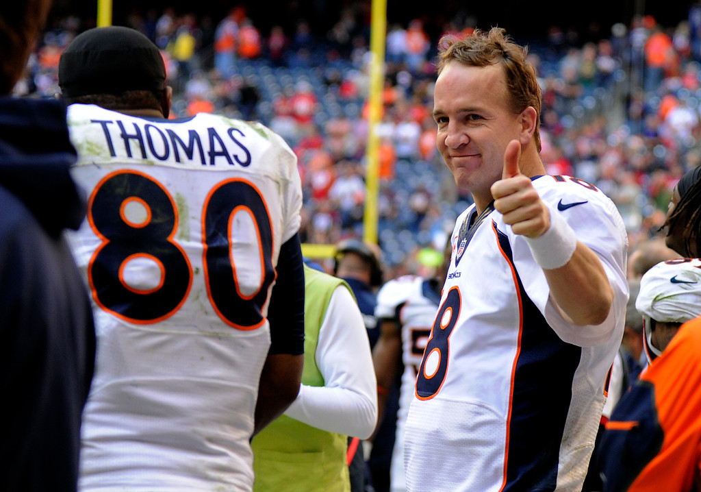 . HOUSTON, TX - DECEMBER 22: Denver Broncos quarterback Peyton Manning (18) gives the thumbs up after talking to Broncos tight end Julius Thomas (80) on the bench after throwing his record breaking 51st pass to him for a touchdown in the fourth quarter against the Houston Texans December 22, 2013 at Reliant Stadium. (Photo by John Leyba/The Denver Post)